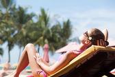 Happy young woman in bikini enjoying her time on chaise-longue luxury pool side — Stock Photo