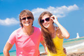 Closeup of happy young caucasian couple in sunglasses smiling on beach — Stockfoto