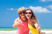 Closeup of happy young couple on beach smiling and hugging. Thumbs up — Stockfoto