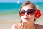 Portrait of young woman in sunglasses blowing an air kiss on beach — Stock Photo