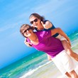 Happy couple piggybacking cheerful on beach thumbs up — Stock Photo #42459135
