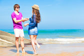 Young woman walking to a young man on tropical beach. relationship. flirting — Stock Photo