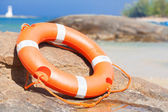 Orange lifebuoy on rocks at sea side. lifesaving equipment. concept — Stock Photo