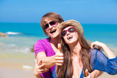 Front view of happy young couple in sunglasses hugging on tropical beach — Stock Photo