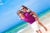 Gelukkige paar meeliften vrolijk op strand duimschroef opwaarts — Stockfoto