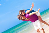 Happy couple in sunglasses on holiday piggybacking cheerful on beach — Stock Photo