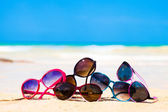 Picture many sunglasses lying on tropical beach — Stok fotoğraf