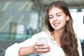 Portrait of happy young woman using mobile phone — Stock Photo