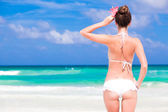 Back view of beautiful young woman in bikini standing on tropical beach. relaxing — Stock Photo