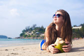 Young woman smiling lying in sunglasses in sunglasses with coconut on beach — Foto Stock
