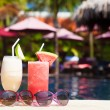 Two glasses of cocktails with fruits near pool — Stock Photo #42641395