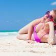 Front view of long haired young woman in bikini lying on tropical beach — Stock Photo #42641577