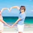 Young happy couple making heart shape on tropical beach. honeymoon — Stock Photo #42641795