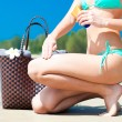 Suntan lotion and sunscreen. Woman applying sunblock cream on leg on tropical beach with beachbag — Stock Photo