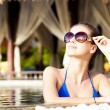 Beautiful young woman in sunglasses with flower in hair smiling in luxury pool — Stock Photo #42642091