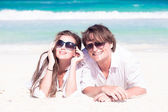Portrait of happy young couple in white clothes in sunglasses lying on beach — Stock Photo