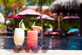 Two glasses of cocktails with fruits near pool — Stock Photo