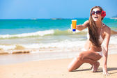 Beautiful young woman holding suntan lotion or cream in plastic bottle on tropical beach — Stock Photo