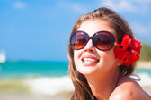 Closeup of young woman in sunglasses smiling on beach — Stock Photo
