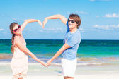 Young happy couple making heart shape on tropical beach. honeymoon — Stock Photo