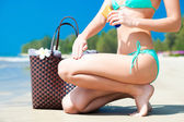 Suntan lotion and sunscreen. Woman applying sunblock cream on leg on tropical beach with beachbag — Stock Photo