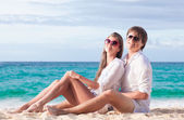 Portrait of happy young couple in sunglasses in white clothes sitting on tropical beach — Stock Photo