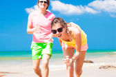 Front view of happy young couple in sunglasses on beach smiling and running — Stock Photo