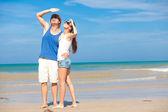 Pareja en ropas brillantes en playa tropical, mirando el cielo — Foto de Stock