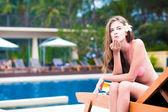 Beautiful young woman in bikini on chaise-longue blowing air kiss — Foto Stock