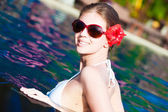 Beautiful young woman in sunglasses with flower in hair smiling in luxury pool — Foto de Stock