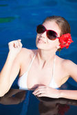 Portrait of Beautiful young woman in sunglasses with flower in hair smiling in luxury pool — Foto de Stock