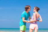 Young couple in bright clothes enjoying their time on tropical beach. holding hands — Stock Photo