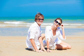 Front view of happy young couple in white clothes in sunglasses lying on beach — Stock Photo