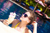 Young attractive smiling woman in sunglasses drinking a cocktail in luxury pool — Stock Photo