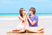 Portrait of happy young couple in sunglasses in bright clothes sitting on tropical beach — Stock Photo