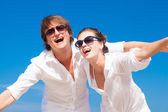 Closeup of happy young couple in white clothes and sunglasses smiling on beach — Stock Photo