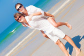 Happy couple in sunglasses and white clothes on holiday piggybacking cheerful on beach — Stock Photo