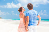 Back view of couple holding hands on tropical beach — ストック写真