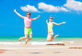 Front view of young couple in bright clothes jumping on the beach — Stock Photo