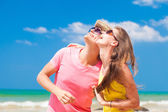 Closeup of happy young couple in sunglasses on beach smiling and looking at sky — Stock Photo