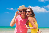 Portrait of happy young couple in sunglasses smiling on beach — Stock Photo