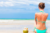 Back view of fit young woman in bikini with coconut on the beach — Stock Photo