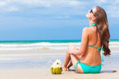 Happy young long haired woman in bikini and sunglasses with coconut on the beach — Stock Photo