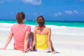 Front view happy young couple in bright clothes in sunglasses sitting on beach — Stock Photo