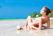 Happy young woman on the beach with coconut cocktail and sunglasses — Foto Stock