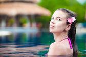 Mulher jovem e bonita com flor no cabelo, sorrindo na piscina de luxo — Fotografia Stock