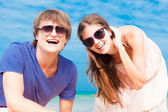 Closeup of happy young couple in sunglasses on beach smiling and looking at sky — Стоковое фото