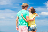 Back view of happy young couple in sunglasses having fun on tropical beach — Stock Photo