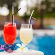 Two glasses of cocktails and sunglasses near pool — Stock Photo #44504431