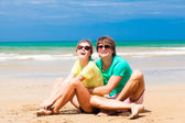 Young happy couple in sunglasses sitting on tropical beach — Stock Photo